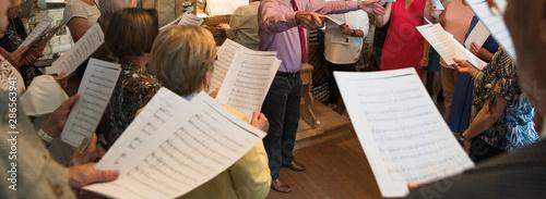 Photographie Probe bei einem Kirchenchor mit Notenblättern und Dirigenten
