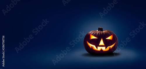 Fotografie, Obraz A halloween lit Jack O Lantern in a spotlight glow on a wide dark blue backgroun