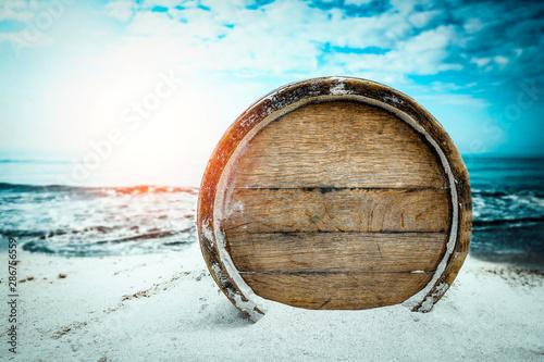 Fotografie, Tablou Old wooden barrel on the sandy beach with dark blue ocean view.