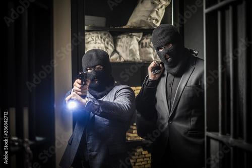 Photo Two ardmed men robbing a bank