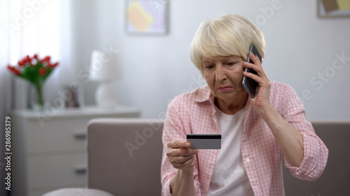 Foto Sad old woman with credit card calling bank support, reporting about money fraud