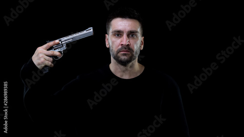 Fotografia Man aiming himself by revolver, life disappointment, suicide commitment, death