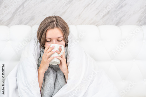 Fotografia Beautiful sick woman sitting on the bed wrapped in a white blanket and drink hot tea