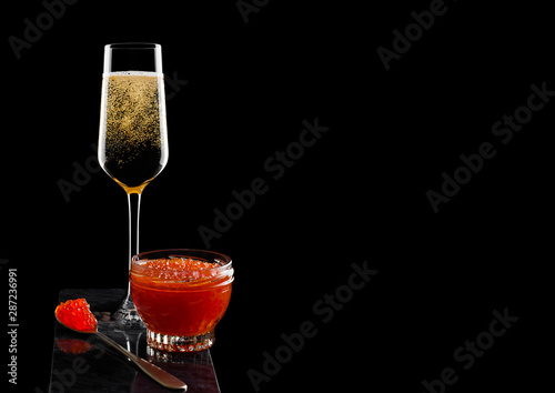 Photo Elegant glass of yellow champagne with red caviar on golden spoon and glass container of caviar on marble board on black background