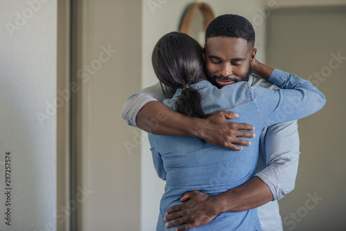 Fotografiet Affectionate young African American man hugging his wife at home