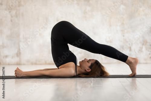 Photo Young woman practicing yoga, Halasana exercise, Plough pose