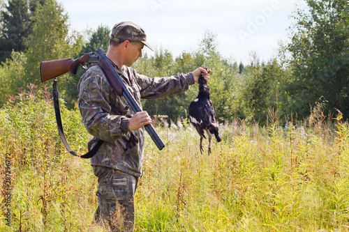 Tablou Canvas hunter with a shotgun holding a downed grouse