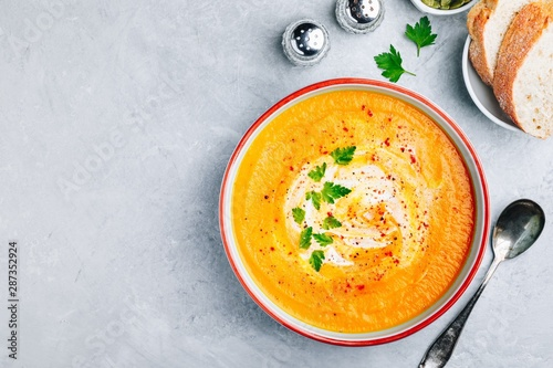 Canvas Print Carrot and pumpkin cream soup with parsley on gray stone background
