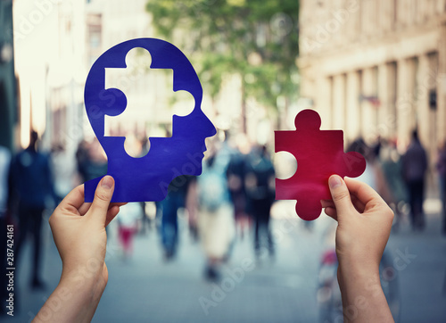 Canvas Print Two hands holding a paper with human head and a puzzle piece