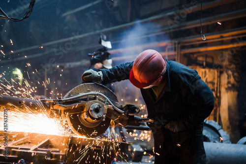 Fotografia, Obraz Industrial worker cutting and welding metal with many sharp sparks
