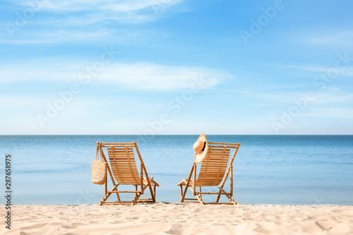 Fotografiet Wooden deck chairs on sandy beach near sea