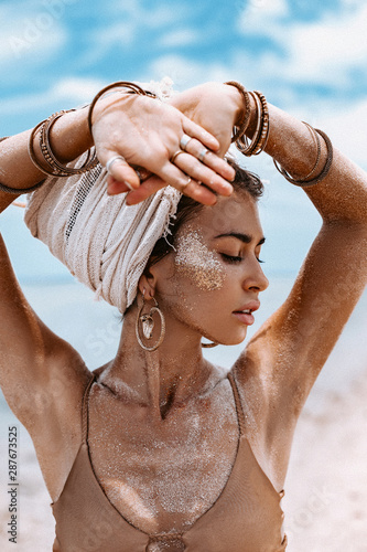Wallpaper Mural close up portrait of beautiful young tribal woman in turban at blue sea and sky