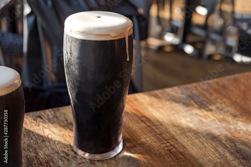 Photo Glass of stout beer cloe-up standing on the wooden table