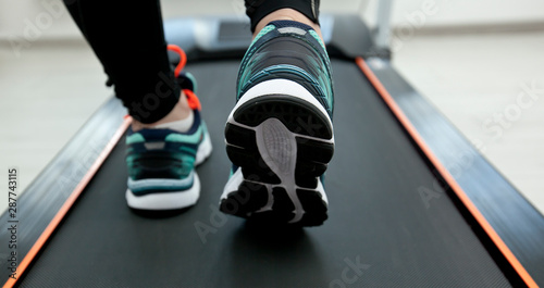 Fotografia The woman's legs in new sneakers on the treadmill