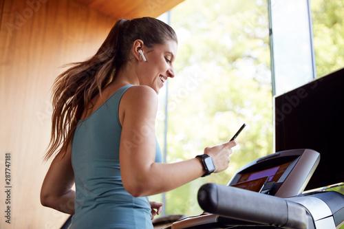 Fotografia Woman Exercising On Treadmill Wearing Wireless Earphones And Smart Watch Checkin