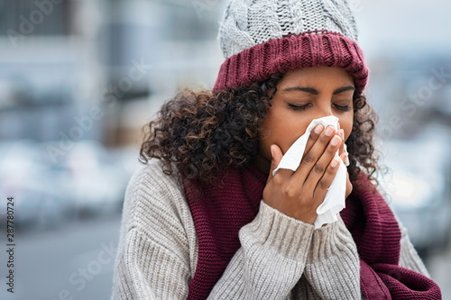 Foto Black woman with cold sneezing outdoor