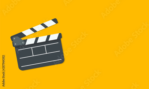 Fotografiet Open clapperboard isolated on yellow background