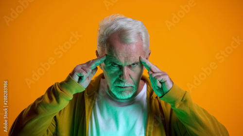 Photographie Elderly male mentalist demonstrating mind-reading power at camera, telepathy