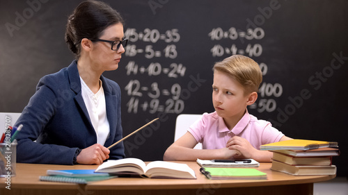 Fotografia Scared schoolboy cautiously looking at strict teacher with pointer, education