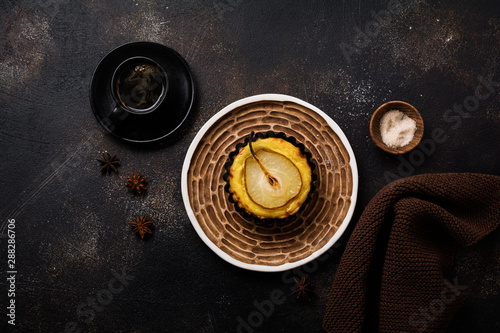 Pears and custard mini tarts on a dark brown concrete old table background Fototapete