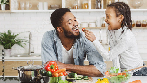 Canvas Print Cute african girl giving her dad cherry tomato while cooking