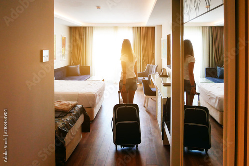 A girl comes into a bright hotel room with a suitcase on wheels. Check in at the hotel.
