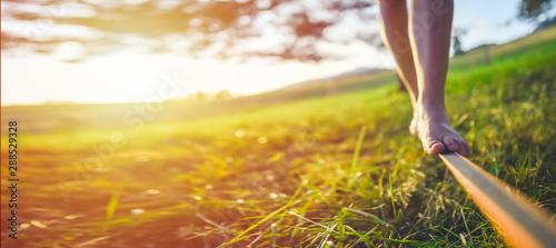Fotografia Close up on feet walking on tightrope or slackline outdoor in a city park in sun shine light - slacklining, balance, training concept