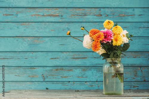 Stampa su Tela Fall flowers in glass jars standing on the table outside