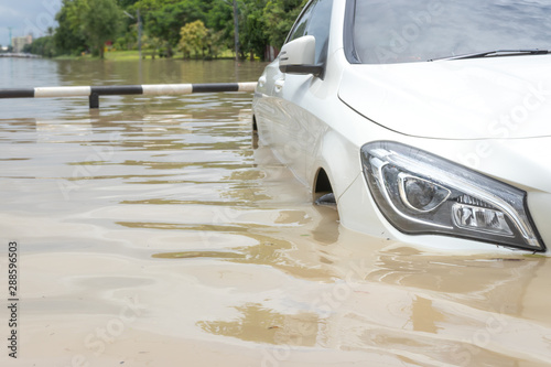 Stampa su Tela Car driving on a flooded road, The broken car is parked in a flooded road