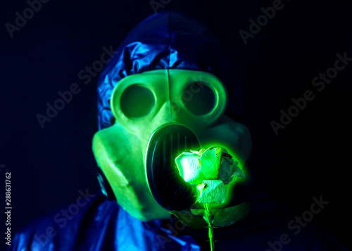 Stampa su Tela Man in the gas mask holding radioactive luminous flower