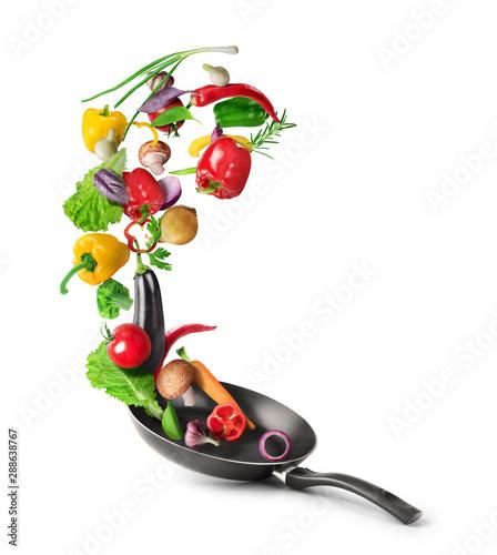 Koncepcja gotowania. Warzywa lecą z patelni na białym tle. Zdrowe jedzenie.