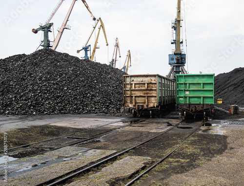 Valokuva loading unloading of coal in the port into freight trains using large port crane