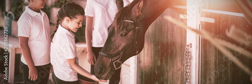 Fotografie, Tablou Three kids feeding the horse in stable
