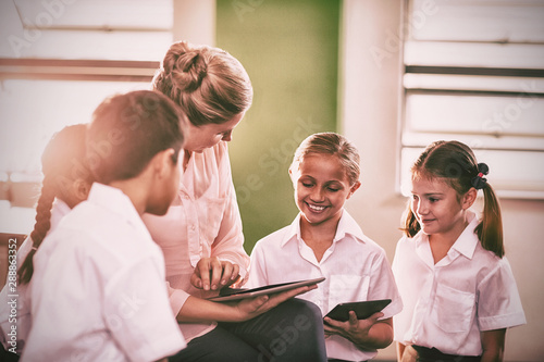 Teacher teaching kids on digital tablet
