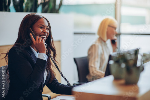 Photo Laughing African American businesswoman working at an office reception desk