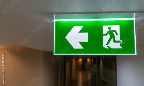 Fotografia Green fire escape sign hang on the ceiling in the office.