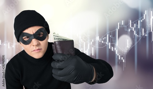 Fotografia Thief in black wear holding wallet with money on background