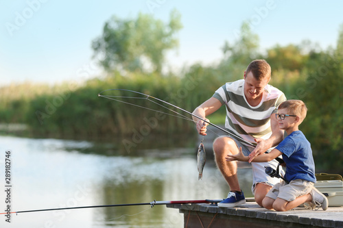 Fotografia, Obraz Dad and son fishing together on sunny day