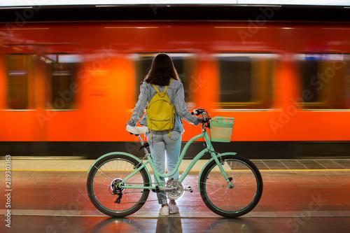 Nastolatka w dżinsach z żółtym plecakiem i rowerem stojących na stacji metra, czekając na pociąg, uśmiechając się, śmiejąc się. Pomarańczowy pociąg przejeżdża za dziewczyną. Futurystyczna stacja metra. Finlandia, Espoo