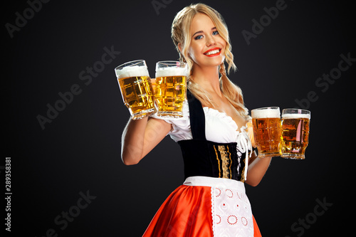 Photographie Young sexy oktoberfest girl waitress, wearing a traditional Bavarian or german dirndl, serving two big beer mugs with drink isolated on black background