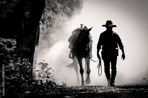 Fotografia black and white picture silhouette of the cowboy and the horse in the morning su