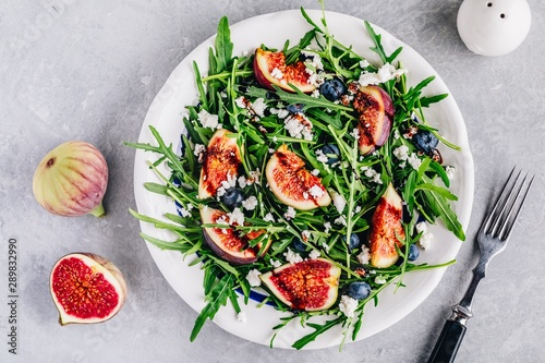 Arugula salad with figs, blueberries and goat cheese, balsamic sauce dressing Fototapeta