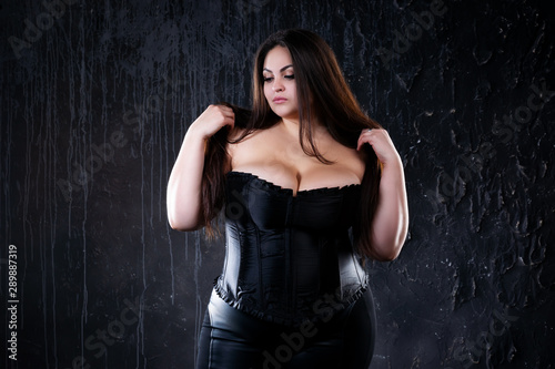 Sexy plus size model in black corset, fat woman with big natural breasts on dark Fototapeta
