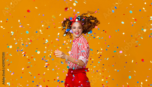 Foto cheerful funny young woman with festive confetti on yellow