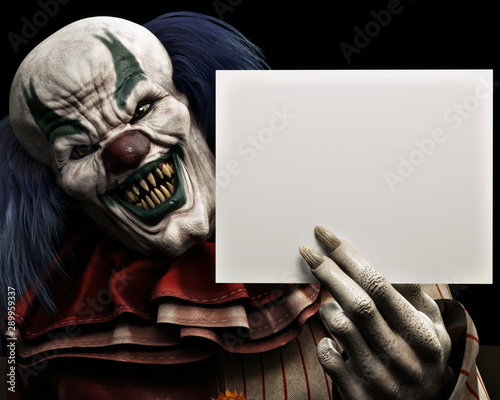 Vászonkép Frightening scary clown with sharp fangs piercing the darkness holding a black advertisment card with room for your text or copy space