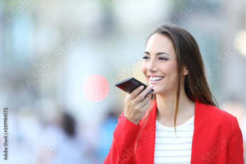 Happy woman in red using voice recognition on phone Fototapete