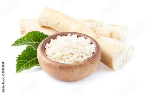 Canvastavla Horseradish root and grated horseradish in wooden plate on white background