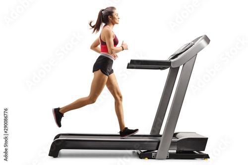 Obraz na płótnie Young sporty female athlete running on a treadmill