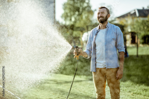 Handsome man watering green lawn, sprinkling water on the grass during a sunny morning on the backyard Fototapeta
