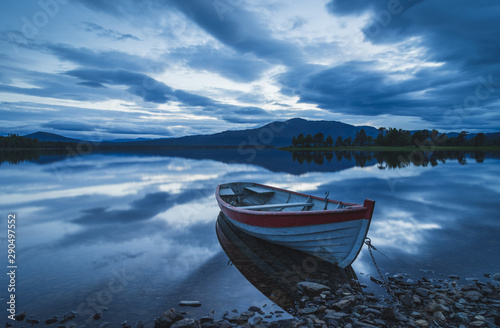 Fotografie, Obraz Old rowing boat at the rocky shore of a lake on a cloudy evening